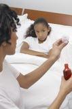 Donna che dà lo sciroppo di tosse alla figlia a letto fotografia stock libera da diritti