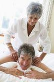 Donna che dà massaggio dell'uomo nel sorridere della camera da letto Fotografie Stock Libere da Diritti