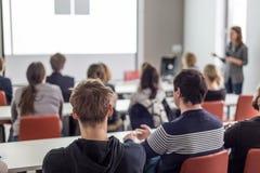 Donna che dà presentazione nel corridoio di conferenza all'università Immagine Stock