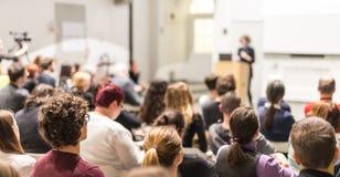 Donna che dà presentazione nel corridoio di conferenza all'università Immagine Stock Libera da Diritti