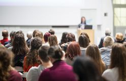 Donna che dà presentazione nel corridoio di conferenza all'università Fotografie Stock Libere da Diritti