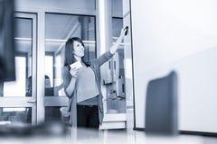 Donna che dà presentazione nel corridoio di conferenza all'università Fotografia Stock