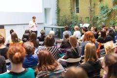 Donna che dà presentazione nel corridoio di conferenza all'università Fotografia Stock Libera da Diritti