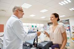 Donna che dà soldi al farmacista alla farmacia Immagine Stock