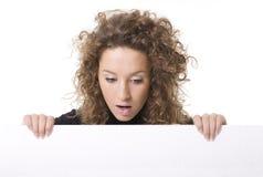 Donna che dà una occhiata dietro il tabellone per le affissioni vuoto fotografia stock libera da diritti