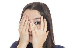 Donna che dà una occhiata dietro la sua mano Immagine Stock