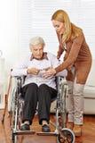 Donna che dà i vetri all'anziano Fotografia Stock