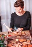 Donna che decora i biscotti del pan di zenzero di Natale con glassare fotografie stock libere da diritti