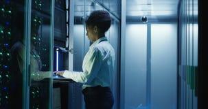 Donna che diagnostica l'hardware del server nel centro video d archivio