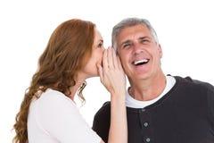 Donna che dice segreto al suo partner Fotografia Stock