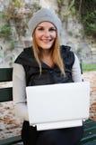 Donna che digita sul sul suoi netbook e sorridere Immagini Stock Libere da Diritti