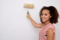 Donna che dipinge la parete della casa fotografia stock libera da diritti