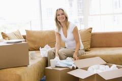 Donna che disimballa le caselle nel nuovo sorridere domestico immagine stock