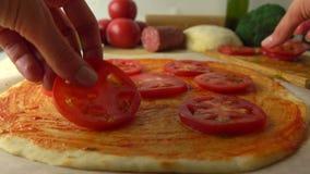 Donna che dispone le fette del pomodoro sopra pizza Cottura, parte dell'insieme 4K si chiudono sul video archivi video
