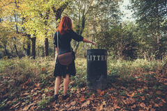 Donna che dispone lettiera nella foresta Fotografie Stock