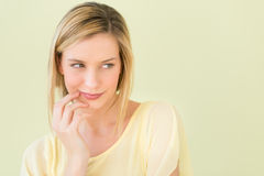 Donna che distoglie lo sguardo contro il fondo verde Immagine Stock