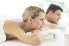 Donna che distoglie lo sguardo mentre rilassandosi alla stazione termale Fotografie Stock
