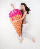 Donna che dorme con il giocattolo del gelato e che sogna di fotografia stock