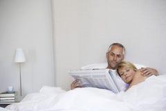 Donna che dorme con il giornale della lettura dell'uomo a letto immagine stock libera da diritti