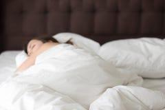 Donna che dorme da solo sul grande letto matrimoniale fotografie stock