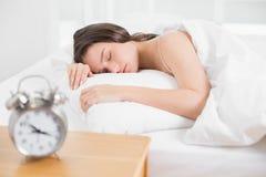 Donna che dorme a letto con la sveglia in priorità alta Immagini Stock