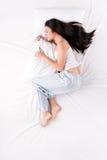 Donna che dorme nella posizione fetale con il cuscino Fotografia Stock Libera da Diritti