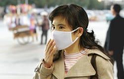 Donna che eleva una maschera di protezione Fotografia Stock Libera da Diritti