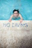 Donna che emerge al poolside Fotografia Stock Libera da Diritti