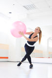 Donna che equilibra con il fitball Fotografie Stock Libere da Diritti
