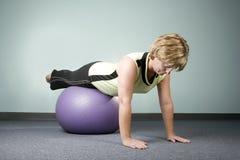 Donna che equilibra su una sfera di esercitazione Immagine Stock Libera da Diritti