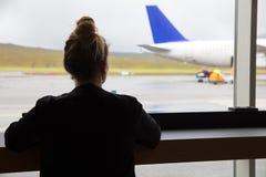Donna che esamina aeroplano attraverso la finestra l'aeroporto Fotografie Stock