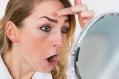 Donna che esamina brufolo in specchio Immagini Stock