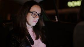 Donna che esamina cellulare mentre nel sedile del passeggero Ragazza con protagonista al suo schermo dello smartphone mentre in a archivi video