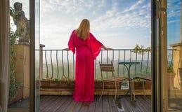 Donna che esamina città da un balcone nel primo mattino fotografia stock