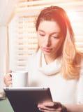 Donna che esamina compressa con la tazza a disposizione Fotografia Stock
