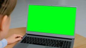 Donna che esamina computer portatile con esposizione verde vuota video d archivio