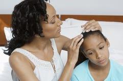 Donna che esamina figlia malata fotografie stock