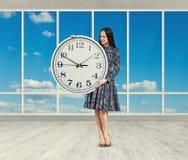 Donna che esamina grande orologio Immagine Stock