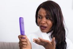 Donna che esamina i capelli di perdita fotografia stock
