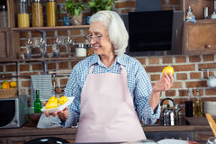 Donna che esamina i limoni in cucina Fotografie Stock Libere da Diritti