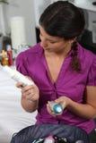 Donna che esamina i prodotti per i capelli Immagine Stock Libera da Diritti