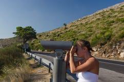 Donna che esamina il binocolo scenico dell'allerta Fotografia Stock Libera da Diritti