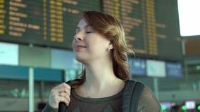 Donna che esamina il bordo di informazioni in aeroporto archivi video