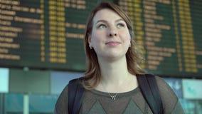Donna che esamina il bordo di informazioni in aeroporto stock footage