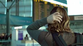 Donna che esamina il bordo di informazioni in aeroporto video d archivio