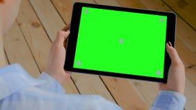 Donna che esamina il computer della compressa con lo schermo verde in bianco - concetto chiave di intensità archivi video