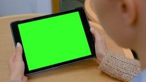 Donna che esamina il computer della compressa con lo schermo verde in caff? stock footage