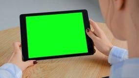 Donna che esamina il computer della compressa con lo schermo verde - concetto chiave di intensità video d archivio