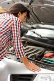 Donna che esamina il motore dell'automobile rotto Immagini Stock