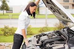 Donna che esamina il motore rotto delle automobili Immagine Stock